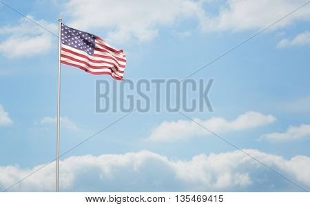 American flag waving on pole against cloudy sky background