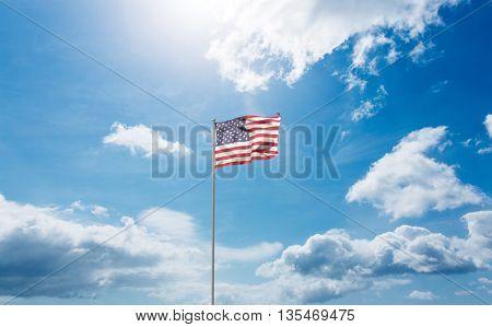 Flag of America on pole against blue sky