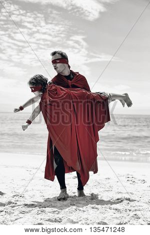 Full length of father in superhero costume lifting son at sea shore