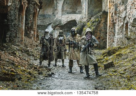 Nuclear post-apocalypse. Survivors in tatters and gas mask on the ruins of the destroyed city