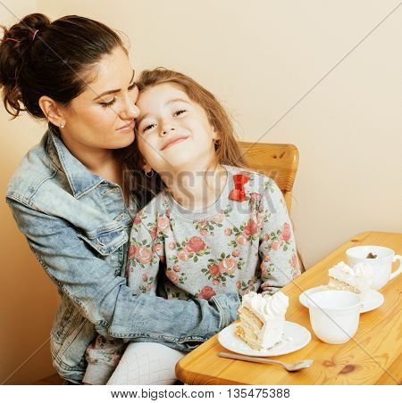 young mother with daughter on kitchen drinking tea together hugging eating celebration cake birthday, lifestyle people concept