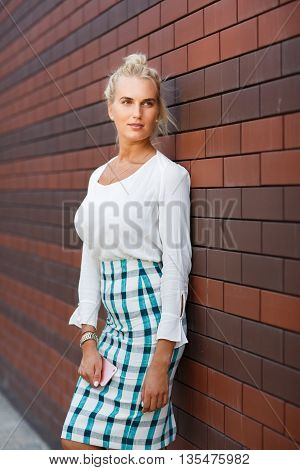 Young cheerful businesswoman leaning on the loft brick wall