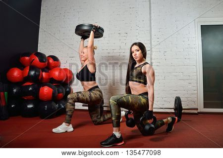Young women doing exercises with kettlebell at gym.