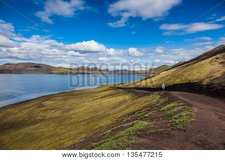 Summer travel to Iceland. Rhyolitic mountains surround the volcanic lake with cold water