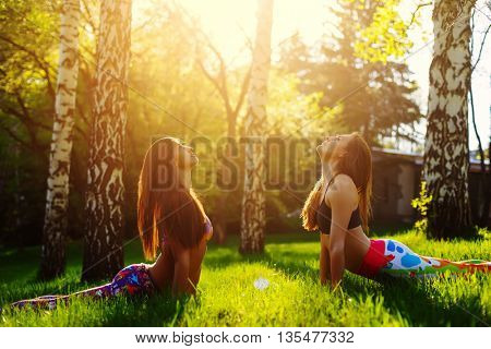 Two young women doing yoga outdoors in the evening