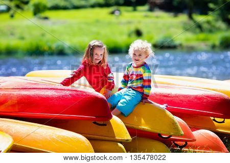 Family on kayak tour. Two kids sitting on pile of kayaks at a river shore on a sunny day. Children in summer sport camp. Active preschoolers kayaking in a lake. Water fun during school vacation.
