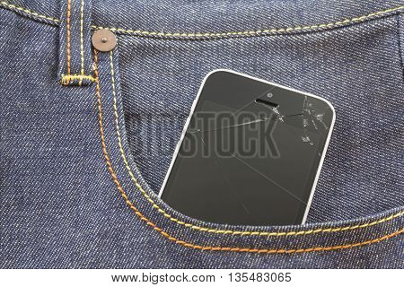 cracked white smartphone screen in blue jeans pocket