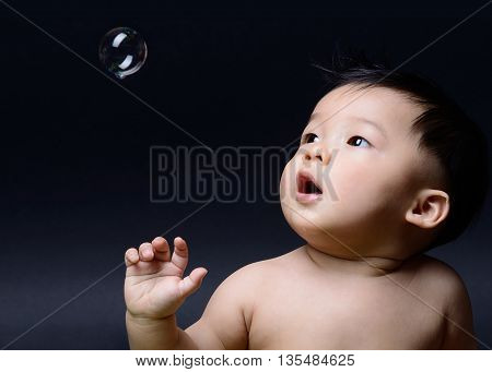 little baby asian boy drooling and looking to soap bubble
