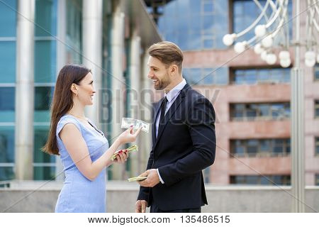 Happy brunette caucasian businesswoman giving a lot of dollars to surprised smiling business men