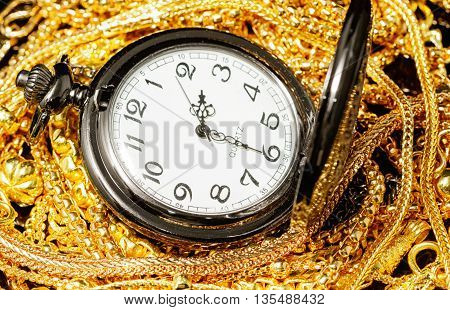 Pocket watch with pile of various golden jewelry isolated black background.