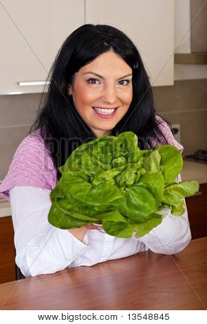 Smiling Woman Holding Fresh Lettuce