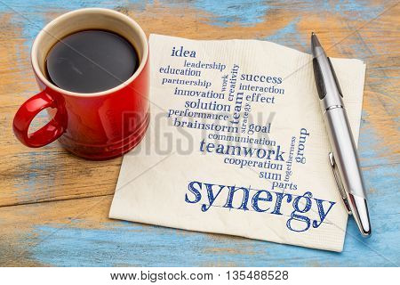 synergy and teamwork word cloud - handwriting on a napkin with a cup of coffee