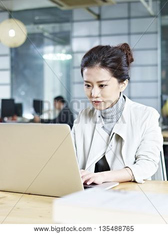 young asian businesswoman working on laptop computer in office.