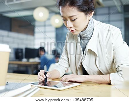 young asian designer working in studio using digital drawing pen and tablet.