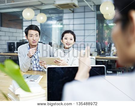 young asian business people talking chatting in office.