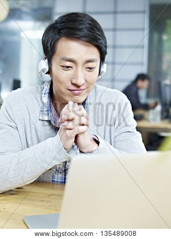 young asian business person looking at laptop computer with listening to music with headphones in office.