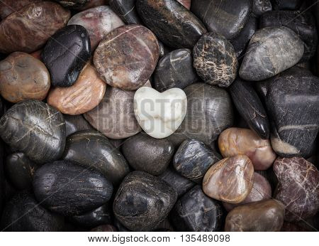 Stones with heart shaped white stones as background