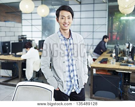 confident young asian entrepreneur standing in own company looking at camera hands in pockets smiling.