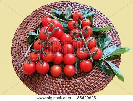 Close up of cherry tomatoes with fresh basil leaves on a wicker plate for vegetarians