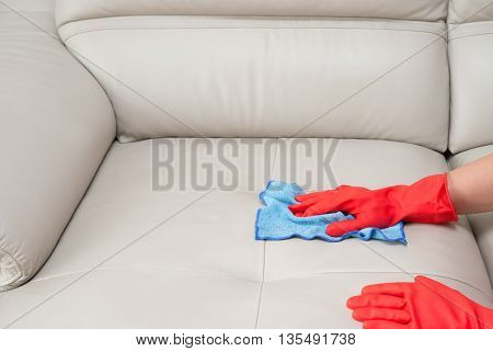 a man cleaning leather sofa at home