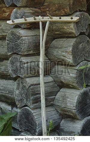 Vintage rake near blockhouse old wall close up