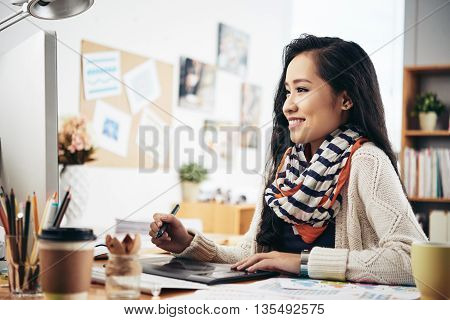 Smiling graphic designer at her work place