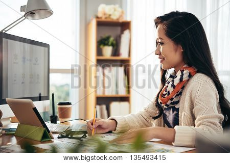 Pretty designer sitting at the table and working with computer