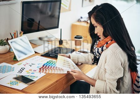 Female designer in office working with color samples