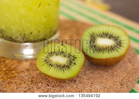 Glass of kiwi juice with fresh kiwis on wooden table