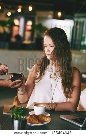 Young woman paying for lunch by credit card at cafe