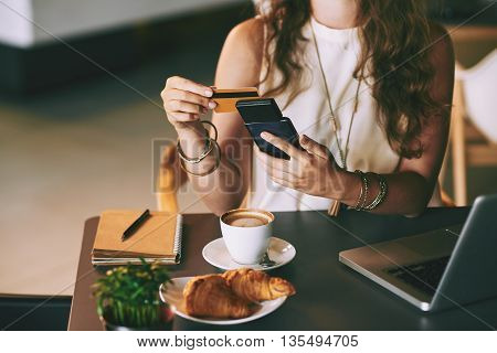 Close-up of woman checking balance on her credit card