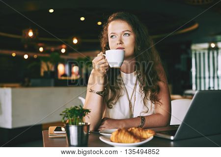 Young woman drinking coffee at cafe alone
