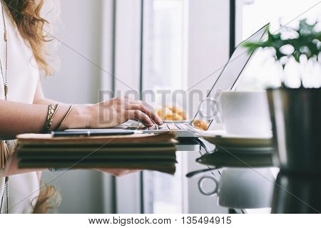 Close-up of businesswoman typing on laptop in cafe