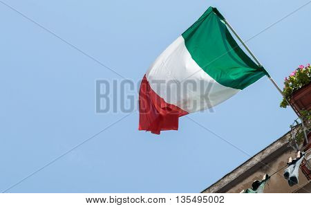 Italian flag flapping in breeze against blue sky