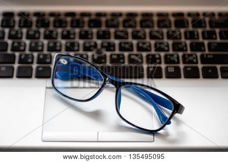 close-up of businessman glasses on laptop computer. in the coffee shop under morning sunlight. (soft focus)