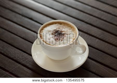 Cappuccino Hot coffee cup on a wooden table vintage tone and soft focus