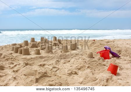 Sandcastle on the beach with toy bucket and shovel