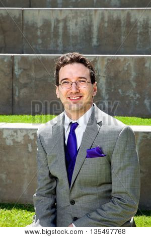A groom sits outside on his wedding day. He is wearing a grey suit with purple tie and handkerchief.