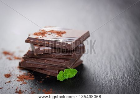 Stack of chocolate chunks with mint on a dark stone background with cocoa closeup horizontal with copy space