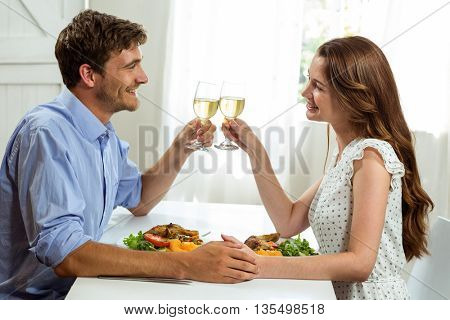 Happy couple toasting wineglasses while having lunch at home