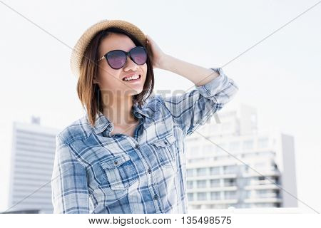 Young woman looking away and smiling outdoors