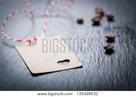 Paper tag with heart on a dark stone background with coffee on a background, closeup