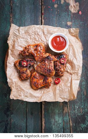 Roasted barbecue chicken wings with bbq sauce italian herbs olive oil and pepper top view