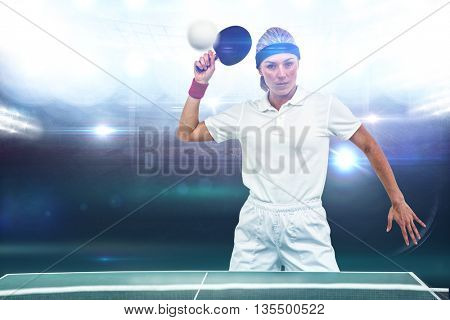 Composite image of female athlete playing ping pong in a stadium