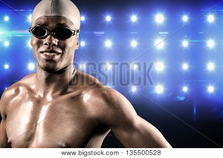 Composite image of swimmer standing with hand on hip against spot light