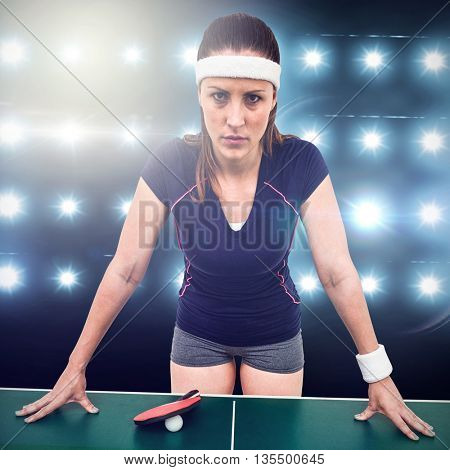 Angry female athlete leaning on hard table against digitally generated image of blue spotlight