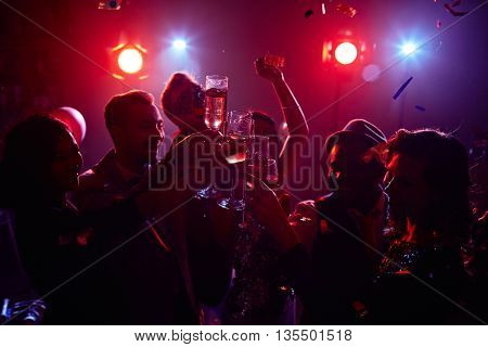 Young people clinking flutes sparkling in neon light