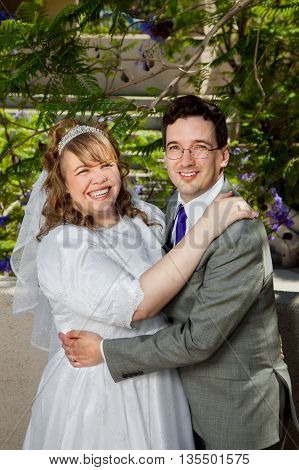 A couple on their wedding day. They have great big just married smiles.