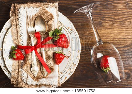 Tableware and silverware with red ripe strawberry on the wooden background