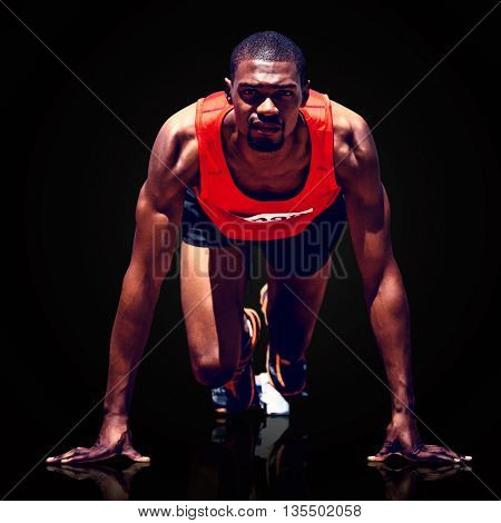 Composite image of athlete man in the starting block against black background